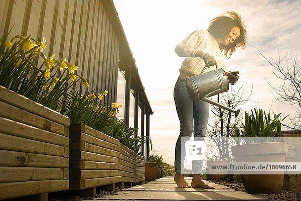 Mittlere erwachsene Frau beim Blumen gießen