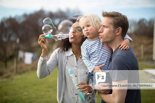 Mother blowing bubbles  father holding son