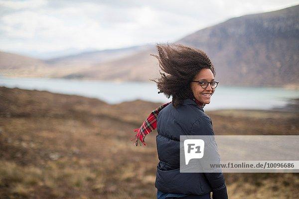 Mittlere erwachsene Frau in den Bergen mit Blick auf die Kamera