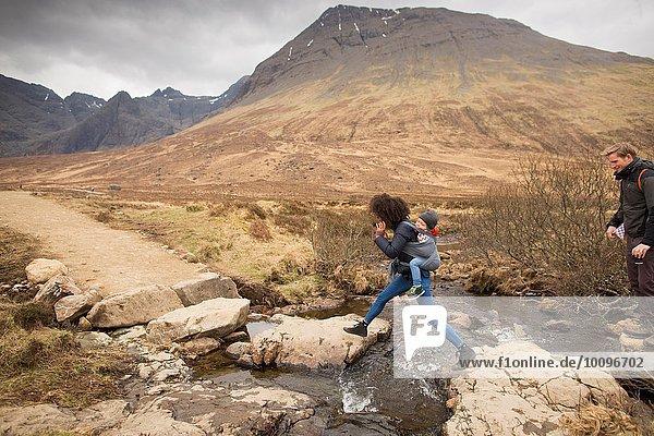 Frau springt über Bach  Fairy Pools  bei Glenbrittle  Isle of Skye  Hebrides  Schottland