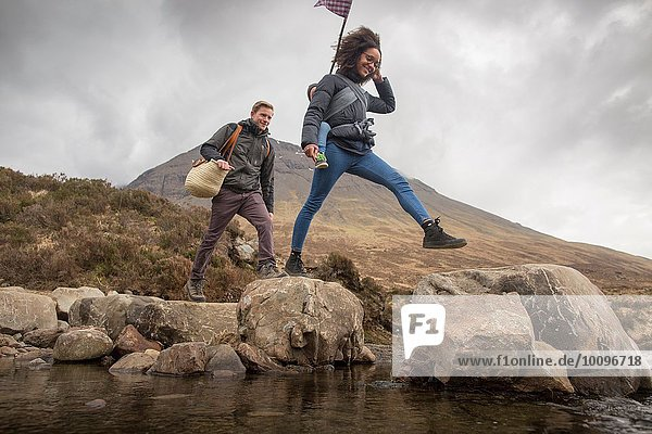 Paar überquert Fluss  Fairy Pools  bei Glenbrittle  Isle of Skye  Hebriden  Schottland