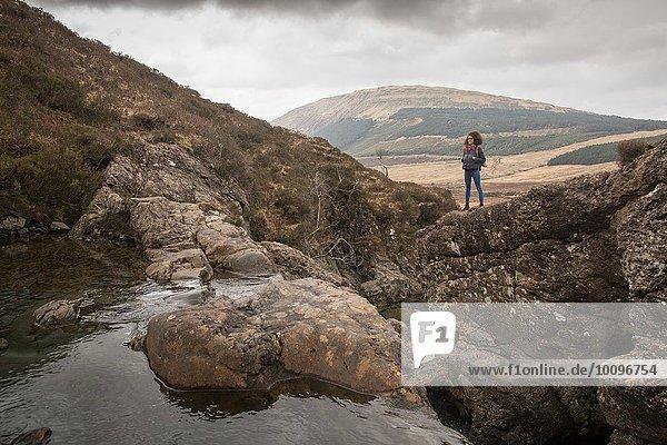 Frau auf Felsen stehend  Fairy Pools  Isle of Skye  Hebrides  Schottland