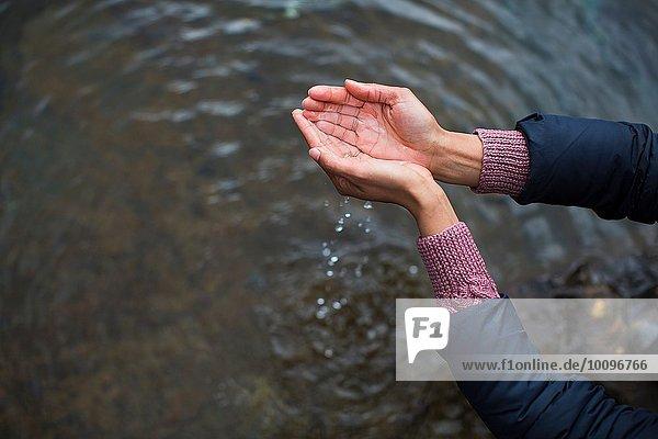 Frau hält Wasser in hohlen Händen