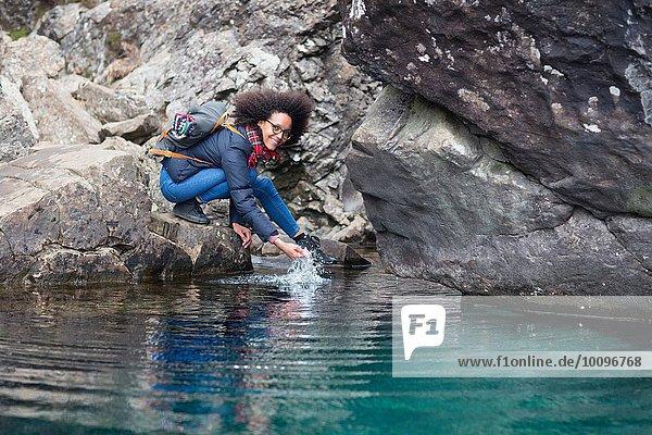 Mittlere erwachsene Frau kauernd am Teich