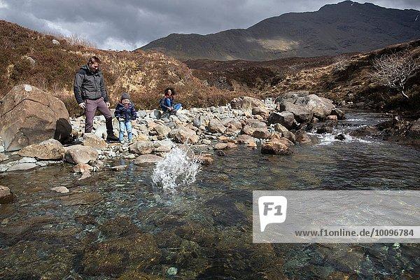 Familie werfen Steine in Teich  Fairy Pools  Isle of Skye  Hebriden  Schottland
