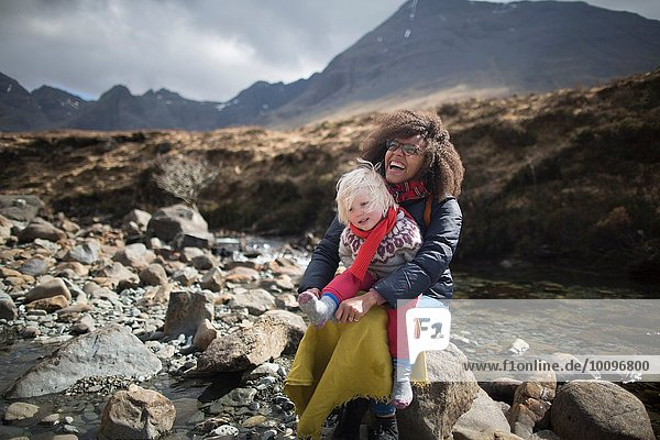 Mutter und Sohn sitzen auf Felsen  Fairy Pools  Isle of Skye  Hebrides  Schottland