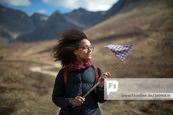 Mittlere erwachsene Frau hält Fahne  schaut weg
