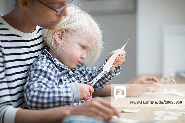 Junge benutzt eine Schere  um mit seiner Mutter Papier zu schneiden.