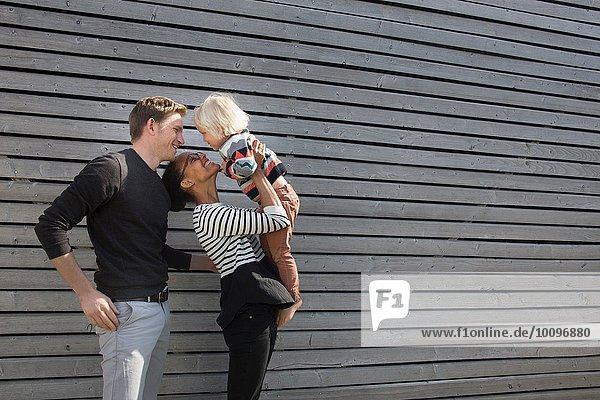 Familie durch Schindelwand  Mutter hält Sohn