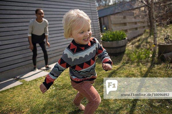 Junge läuft im Garten  lächelnd
