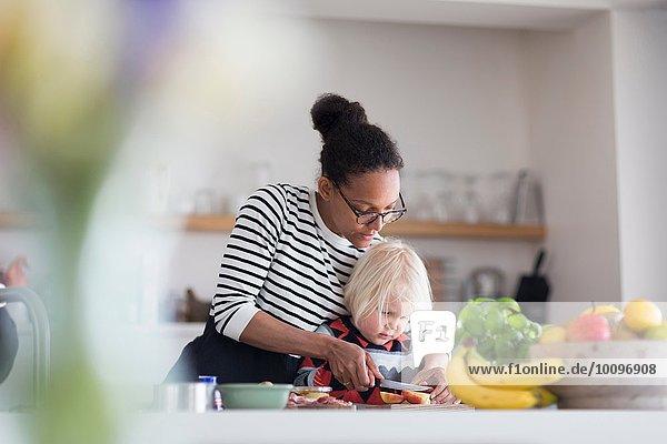 Mutter hilft dem Sohn bei der Zubereitung des Essens in der Küche