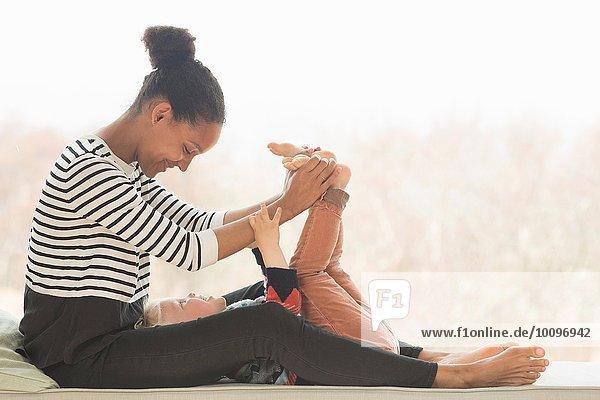 Mutter spielt mit dem Sohn  hält seine Füße.