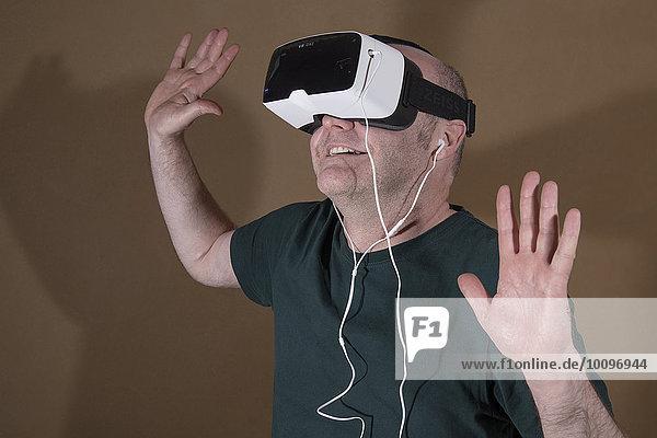 Mann trägt ZEISS VR ONE Virtual Reality Kunststoff-VR-Brille mit Halterung für Samsung Galaxy S5 Android Smartphone und In-Ear Kopfhörer  Hände oben