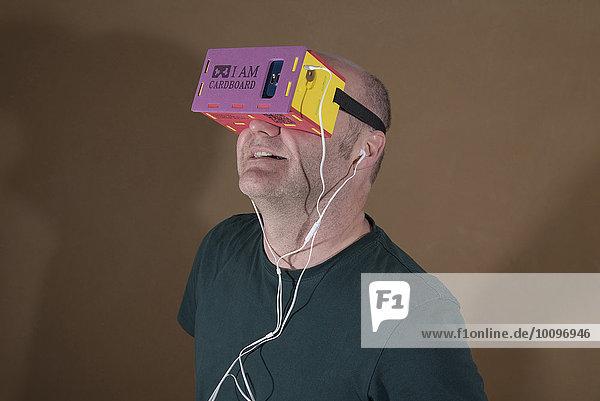 Mann trägt I AM CARDBOARD 45mm Focal Length Virtual Reality Google Cardboard-VR-Brille mit Samsung Galaxy S5 Android Smartphone und In-Ear Kopfhörer