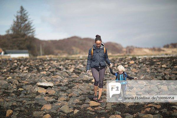 Mutter und Sohn halten sich an den Händen und gehen auf Felsen.