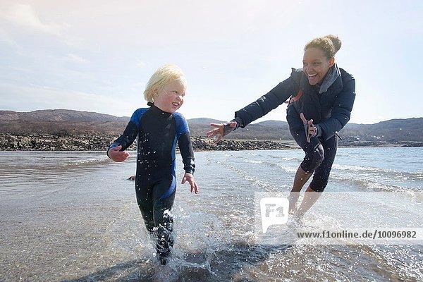 Mutter und Sohn laufen am Strand  Loch Eishort  Isle of Skye  Hebrides  Schottland