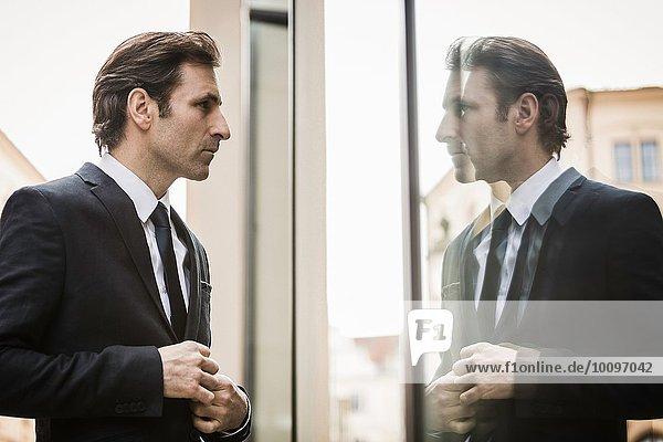 Der reife Geschäftsmann  der das Spiegelbild im Fenster betrachtet.