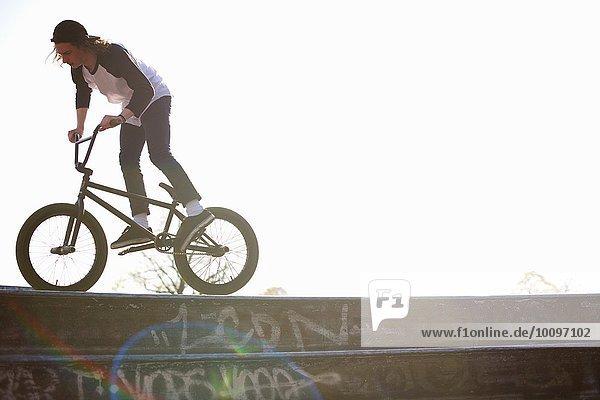 Junger Mann beim Stunt auf bmx im Skatepark