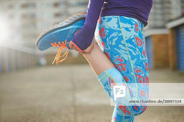 Ausschnitt aus der Sicht der Frau beim Beugen des Beines und Dehnen vor dem Training
