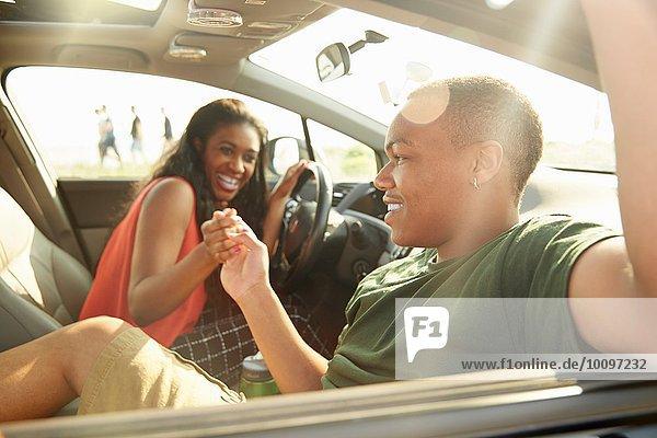 Junges Paar  das im Auto sitzt und Händchen hält
