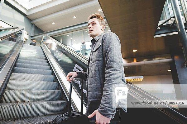 Junger Geschäftsmann Pendler auf Rolltreppe mit Koffergriff.