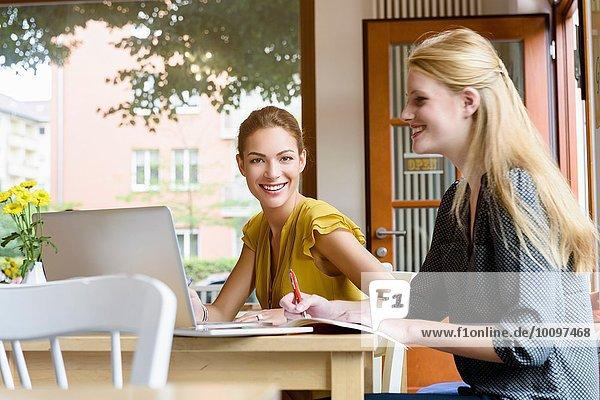 Zwei junge Frauen mit Laptop und Notizen im Cafe