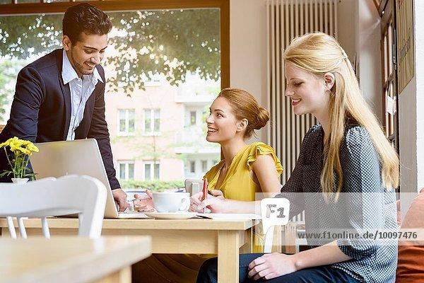 Junger Mann im Gespräch mit junger Frau im Cafe