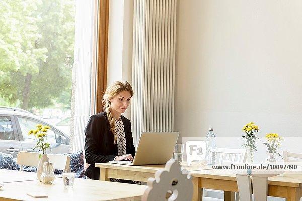 Junge Frau beim Tippen am Laptop im Cafe