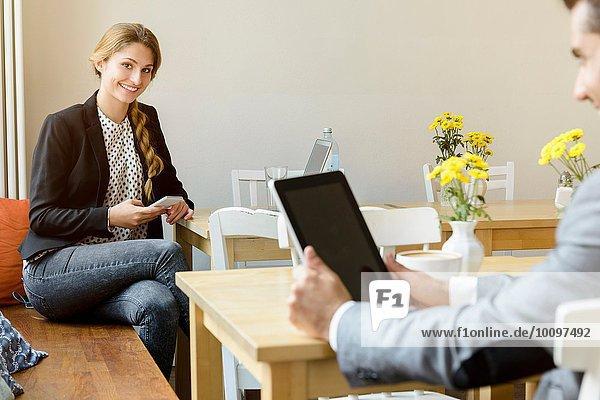 Junge Frau und Mann im Café mit Laptop und digitalem Tablett