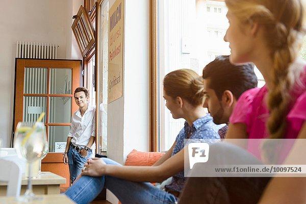 Junge erwachsene Freunde  die den Teenager in der Cafeteria anschauen.