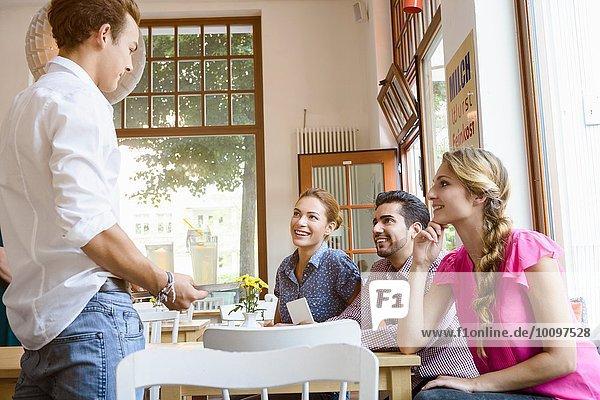 Kellner nimmt Bestellung von jungen erwachsenen Freunden im Cafe entgegen.