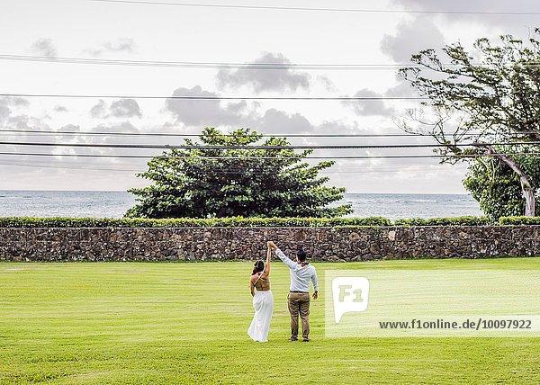Rückansicht von Braut und Bräutigam mit erhobenen Händen im Garten der Hawaiianischen Hochzeit  Kaaawa  Oahu  Hawaii  USA