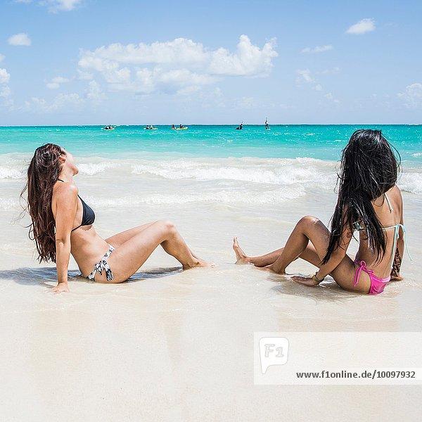 Side view of two young women sitting on Kailua beach  Oahu  Hawaii  USA