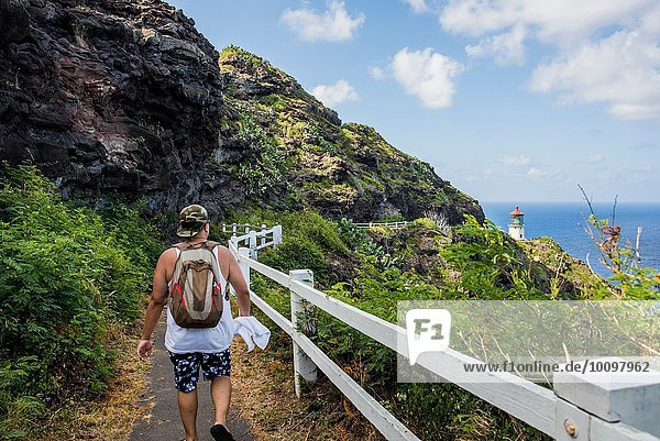 Rückansicht eines jungen männlichen Touristen  der zum Leuchtturm von Makapuuu  Oahu  Hawaii  USA geht.