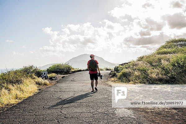 Junge männliche Touristen mit digitaler Spiegelreflexkamera auf dem Makapuuu Küstenweg  Oahu  Hawaii  USA