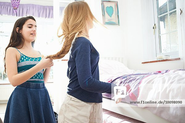Teenager-Mädchen flechten beste Freunde Haare im Schlafzimmer