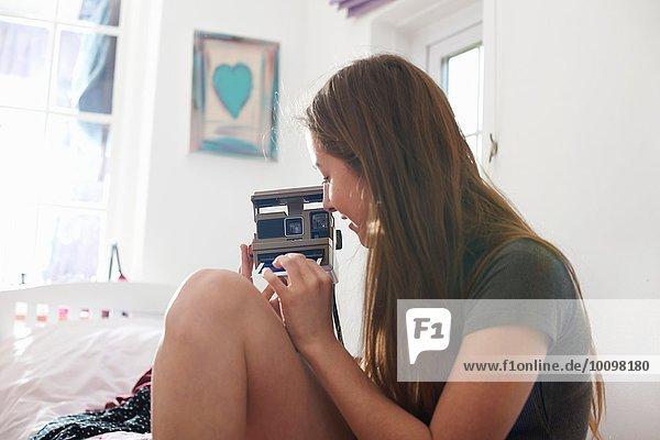Teenagermädchen im Schlafzimmer entfernt Sofortbild von der Kamera