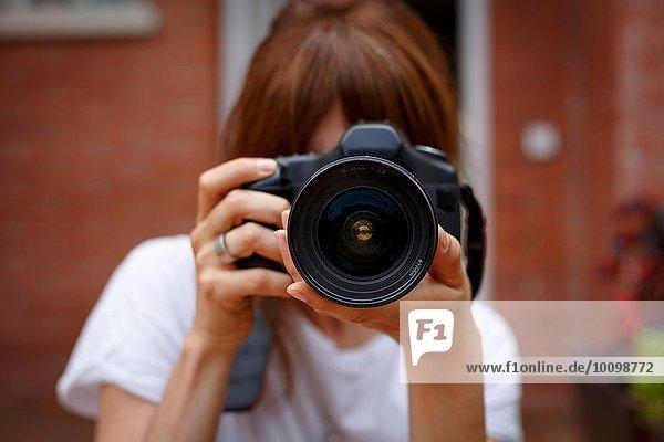 Mittlere erwachsene Frau mit Digitalkamera,  Gesicht verdeckt