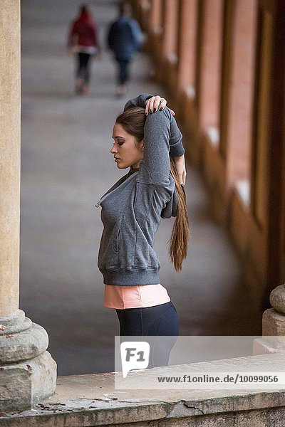 Junge Frau in Sportbekleidung mit ausgestreckten Armen
