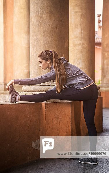 Junge Frau in Sportbekleidung  die die Beine streckt