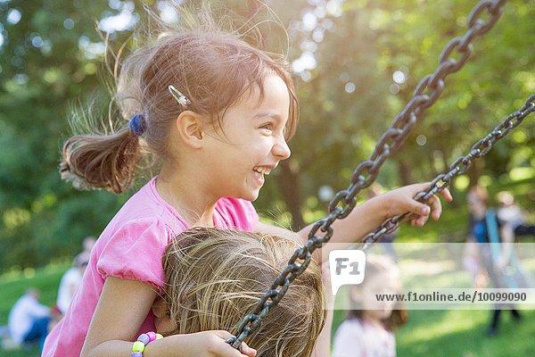 Zwei junge Mädchen  die zusammen auf der Parkschaukel schwingen.