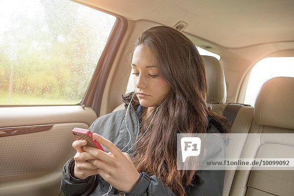 Sullen Teenager-Mädchen Auswahl Smartphone-Musik im Auto Rücksitz