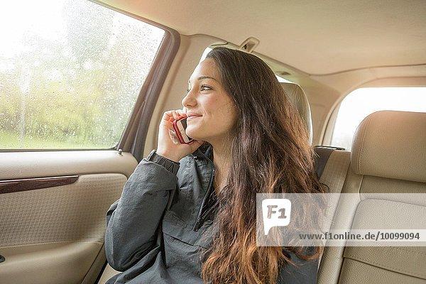 Teenager-Mädchen beim Chatten auf dem Smartphone auf dem Rücksitz im Auto