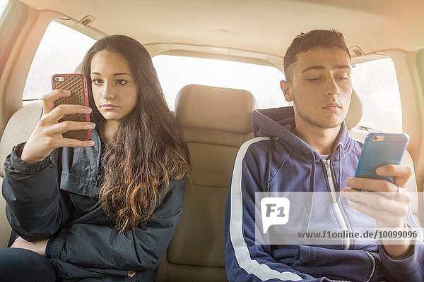 Teenager-Mädchen und junger Mann lesen separate Smartphone-Texte im Auto Rücksitz