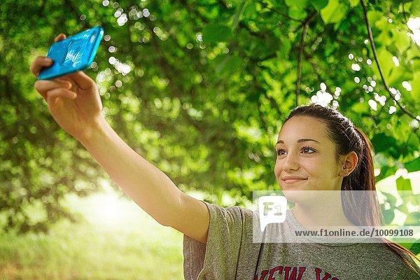 Teenager Mädchen im Park nimmt Smartphone Selfie