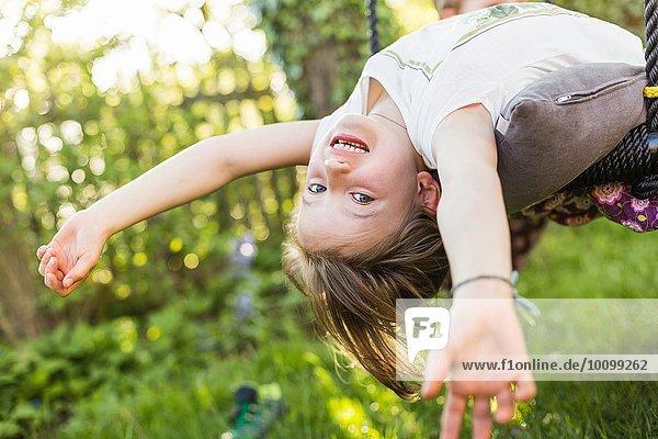 Porträt eines Mädchens  das sich im Garten auf den Kopf gestellt zurücklehnt.