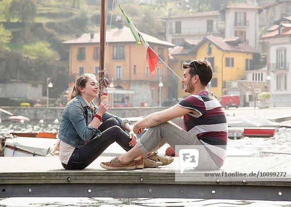 Paar sitzt am Pier und isst Eis am See Mergozzo  Verbania  Piemonte  Italien