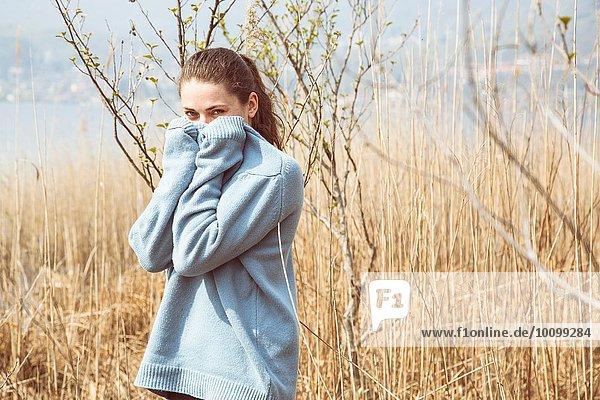 Porträt einer jungen Frau im blauen Pullover am Seeufer  Mergozzo-See  Verbania  Piemonte  Italien