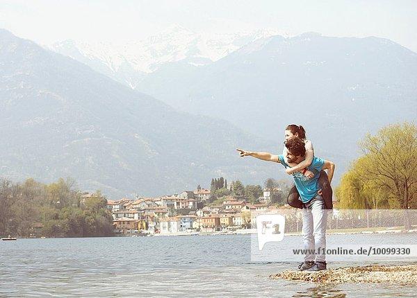 Junger Mann gibt Freundin Huckepack am Seeufer  Mergozzo-See  Verbania  Piemonte  Italien