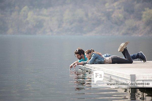 Junges Paar auf dem Pier liegend  tauchende Finger im Mergozzo-See  Verbania  Piemonte  Italien